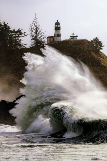 Crashing waves at Cape Disapppointment State Park with the lighthouse.